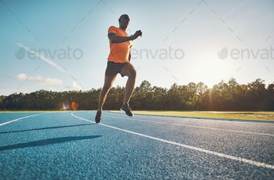Focused young athlete sprinting alone along a running track