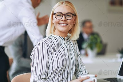 Smiling young businesswoman drinking a coffee at work