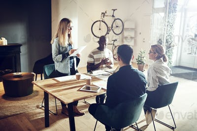 Young woman giving a presentation to coworkers in an