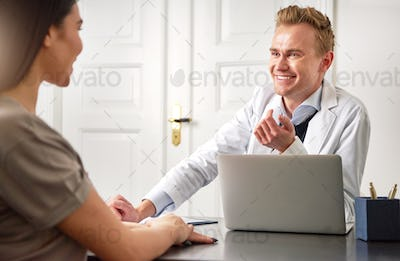 Cheerful beautician talking to young woman sitting at laptop