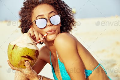 Young woman relaxing at the beach drinking from a coconut