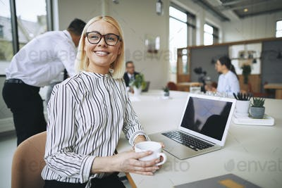 Smiling young businesswoman sitting in an office boardroom drinking coffee