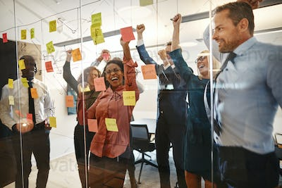 Excited businesspeople cheering together after an office brainstorming session