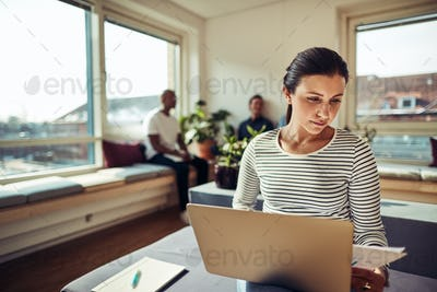 Businesswoman using a laptop and reading documents in an office