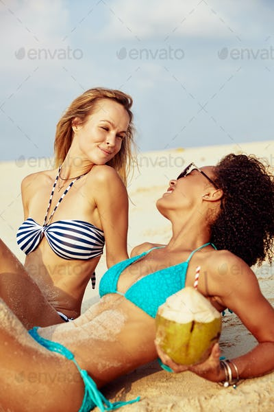 Two smiling female friends suntanning together on a tropical beach
