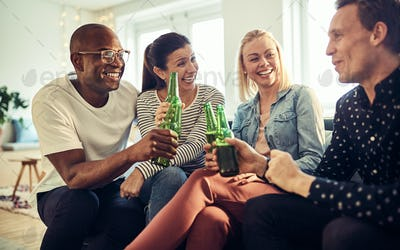 Smiling young businesspeople celebrating together with beers in an office