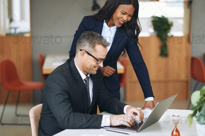 Two smiling diverse businesspeople working together on a laptop