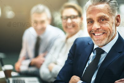 Smiling mature businessman sitting with colleagues at an office table