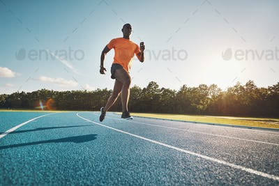 Young African athlete sprinting down a running track