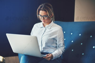 Young businesswoman sitting on a sofa working online