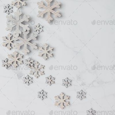 Winter pattern made of snowflakes on marble background. Winter concept. Flat lay.