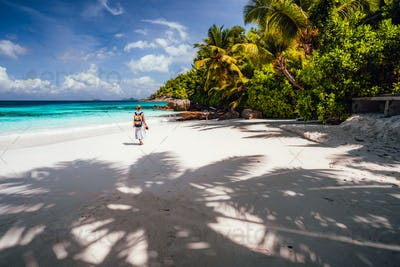 Female tourist enjoy vacation on tropical island with white sand beach, palm trees and blue ocean