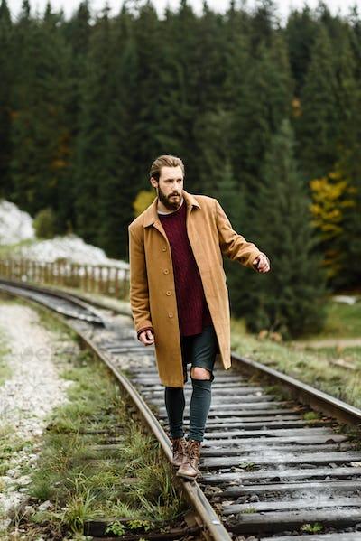 brutal bearded man walks on the tracks