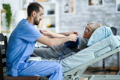 Male caretaker in a nursing home taking bood pressure