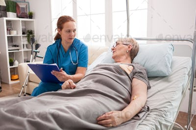 Old woman sitting in bed in nursing home