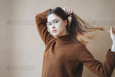 Young beautiful long hair girl with blue eyes in brown knitted sweater looking at camera