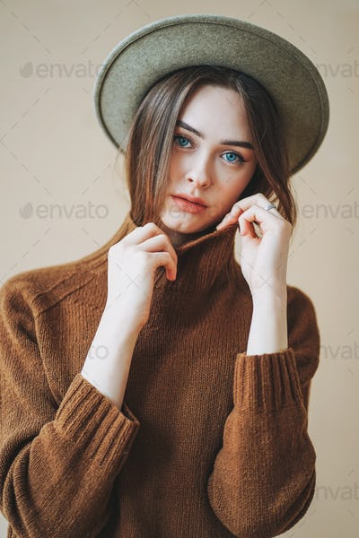 Young beautiful long brown-haired hair girl with blue eyes in felt hat and brown knitted sweater