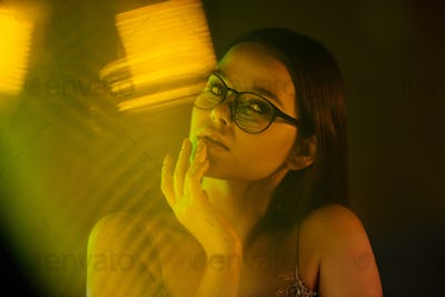 Young attractive female in eyeglasses sitting by window in front of camera