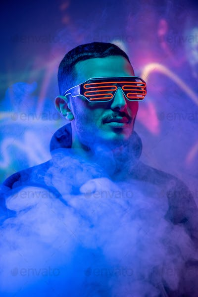 Head of contemporary young mixed-race man in red spiral eyewear among smoke