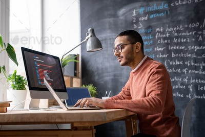 It-manager sitting in front of laptop in office and analyzing coded information