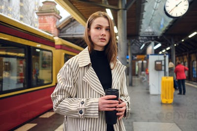 Attractive girl in trench coat with thermo cup waiting train at subway station
