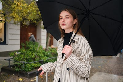 Stylish girl intently looking away while walking around rainy city street with umbrella and suitcase