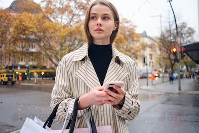 Pretty casual girl thoughtfully walking around city street with shopping bags and smartphone