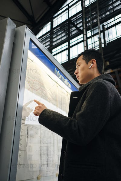 Young stylish Asian businessman in intently watching public transport route at metro station outdoor