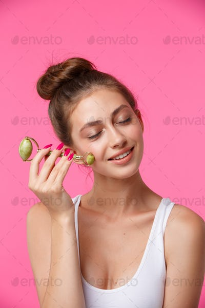 Woman applying jade roller for massaging her face