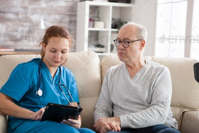 Young female doctor in nursing home taking notes on tablet pc