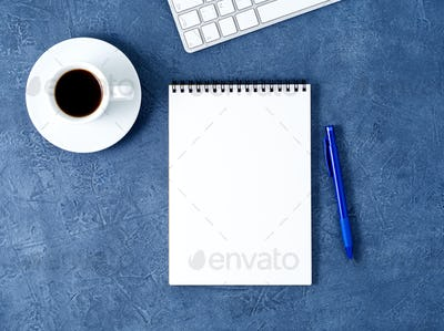 The open notepad with clean white page, pen and coffee cup on aged dark blue stone table, top view