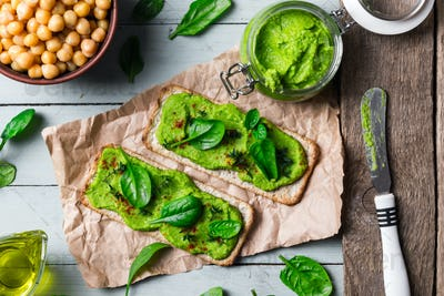 Two crackers with green spinach humus