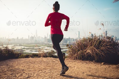 Fitness woman runner running face to the sunset city