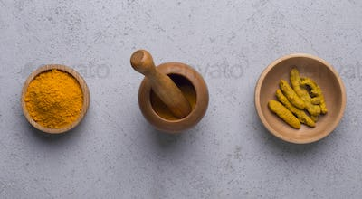 Curcuma in different shapes turmeric powder, root on concrete