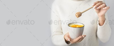 Woman holding cup of latte with turmeric powder and honey