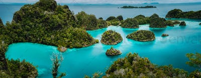 Panoramic view Pianemo Islands, Blue Lagoon with Green lush karst lime stone Rockes, Raja Ampat