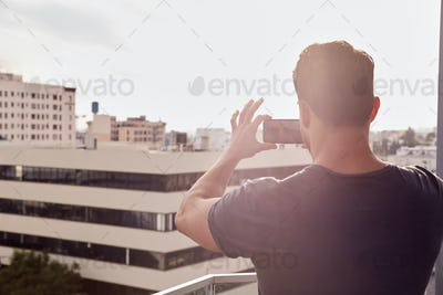 Rear View Of Man Taking Photo Of City Skyline Against Flaring Sun