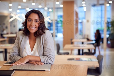 Portrait Of Businesswoman At Desk In Modern Office Work Space With Closed Laptop