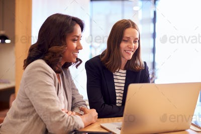 Two Businesswomen With Laptop Collaborating On Project In Office Together