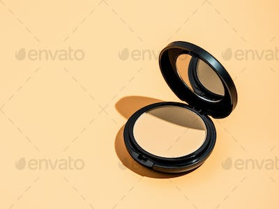 Compact powder on yellow background, copy space