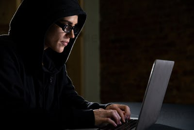 Caucasian woman working on a laptop computer in the dark