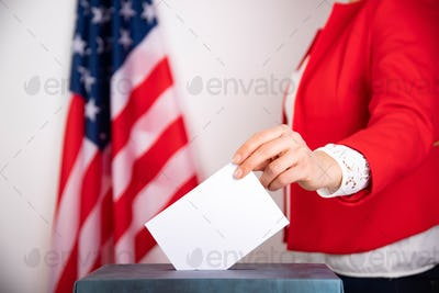 American voter putting ballot into voting box.