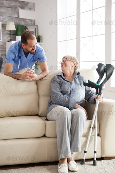Old woman sitting on couch holding her crutches