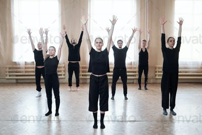 Group of young dancers in black activewear raising arms while training