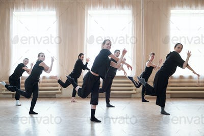 Seven young active men and women in black sportswear training in studio