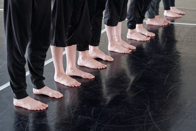 Row of legs of barefoot young dancers in black pants standing on the floor
