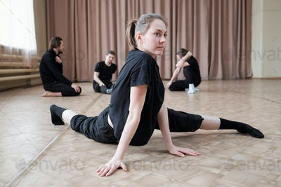 Pretty young flexible female dancer in black activewear exercising on the floor