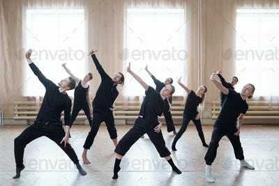 Group of young active dancers in black t-shirts and pants stretching one arm