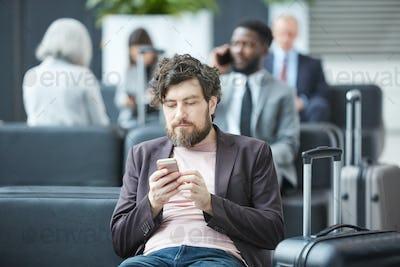 Man Using Smartphone In Departure Lounge