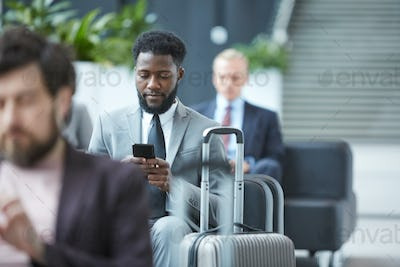 Businessman With Smartphone In Departure Lounge